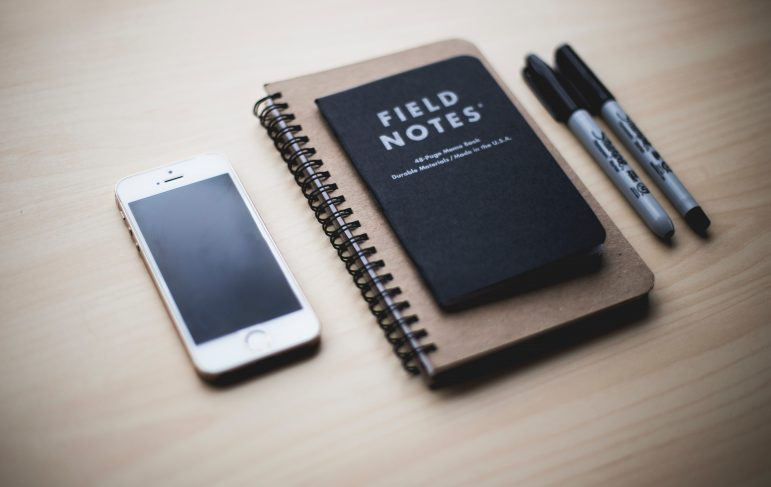 Iphone and sharpies on table with Field Notes spiral notebook.