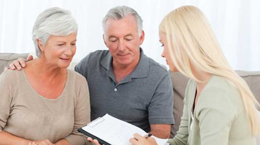 Elderly couple goes over paperwork with a young women.