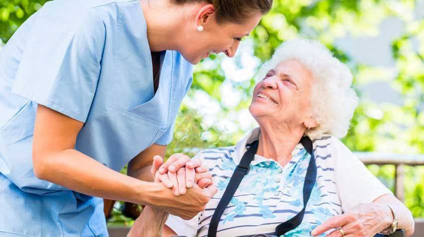 Nurse holds elderly women's hand.